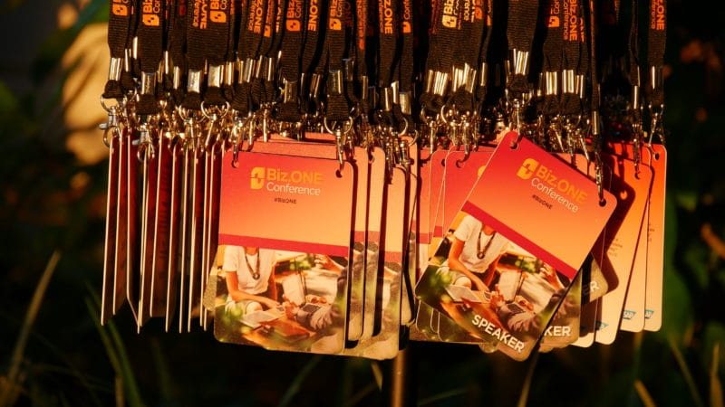 Image of several hanging conference badges that say